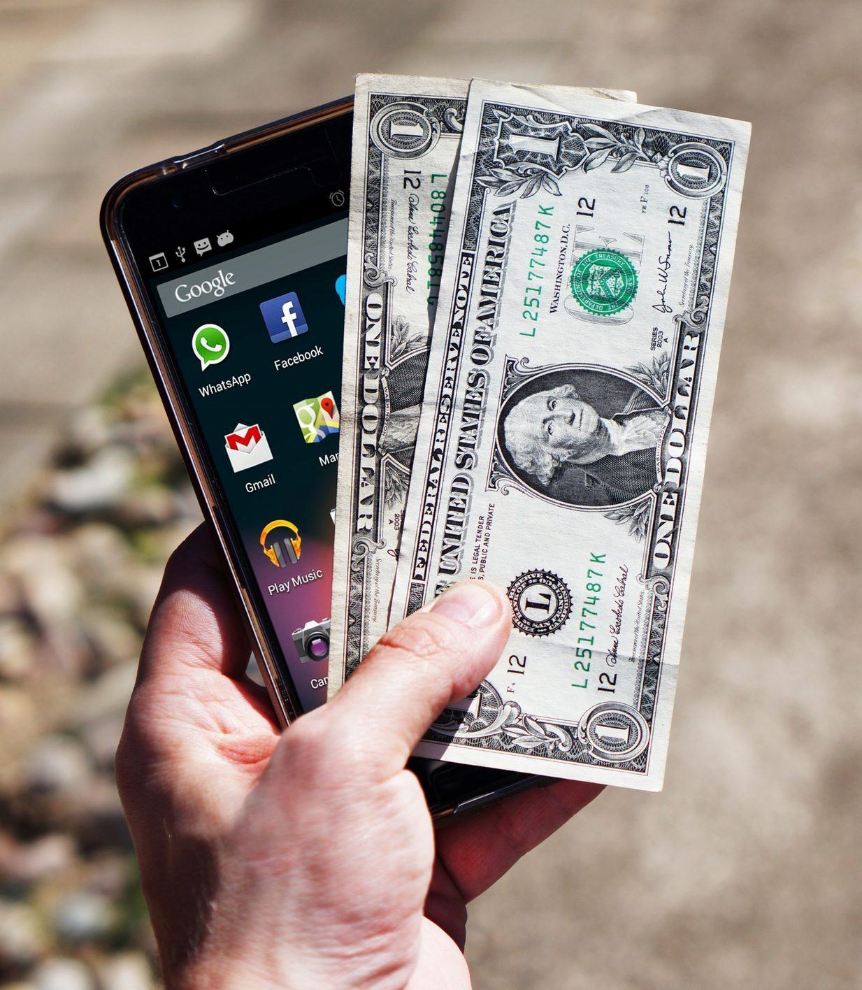 Eine Hand hält ein Smartphone und 2 darüberliegende Geldscheine fest