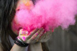 Eine Frau blässt aus ihren Händen eine Wolke rosa Staub.