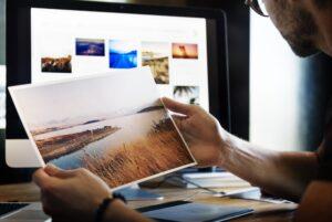 Mann betrachtet Foto neben Computer - zur Veranschaulichung der Google Bildersuche