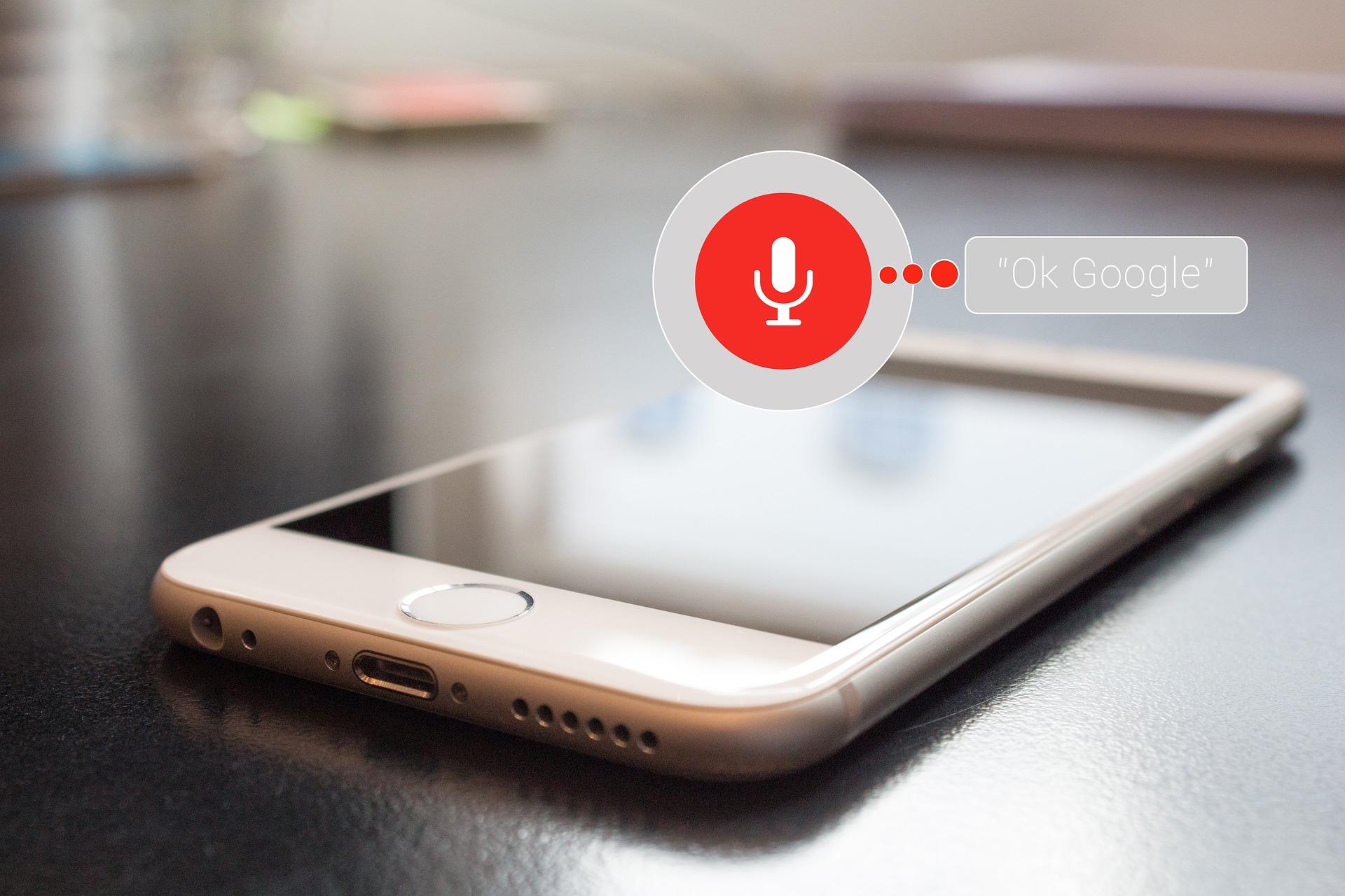 """Helles Smartohone liegt auf einer dunklen Fläche darüber ist ein Icon, das den Sprachbefehl zur Aktivierung der Sprachsuche """"Ok Google"""" abbildet"""