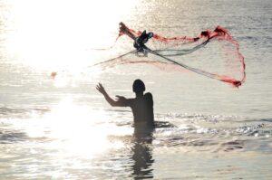 Mensch im Meer mit Fischernetz