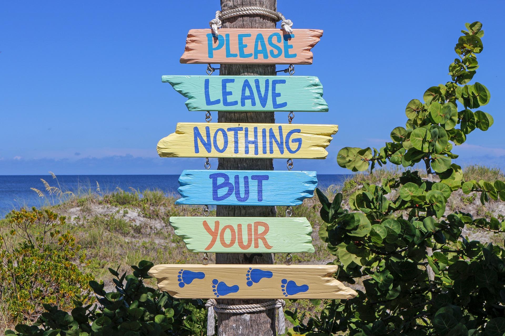 """Schild mit der Aufrschirift: """"Please leave nothing bur your"""" der unterste Teil des Schilds zeigt Fußabdrücke. Das Schild ist mitten im Grünen und dahinter sieht man das Meer."""