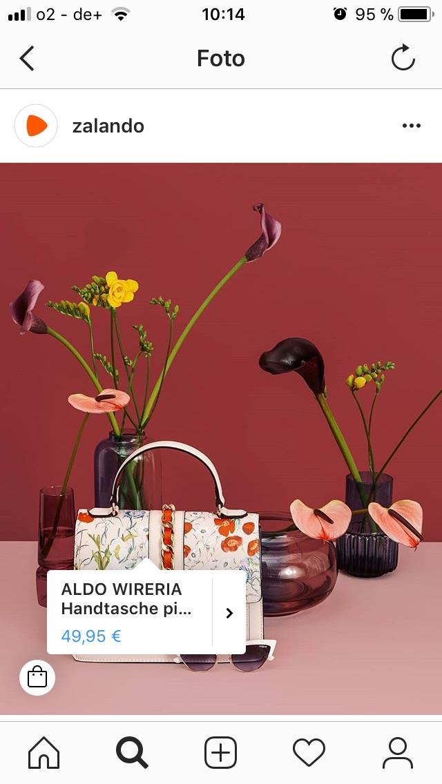 Foto mit kleiner Handtasche im Vordergrund, weißer Sonnenbrille, und 4 Vasen mit Blumen im Hintergrund.
