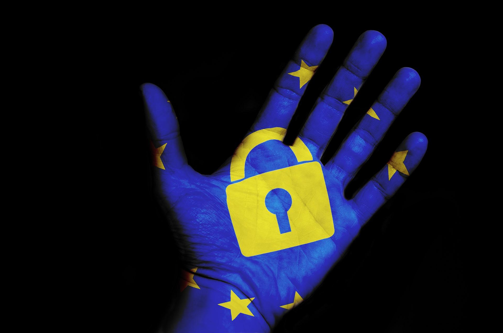 Blaue Hand mit gelben Sternen (EU) und in der Mitter der Hand ist ein gelbes Schloss