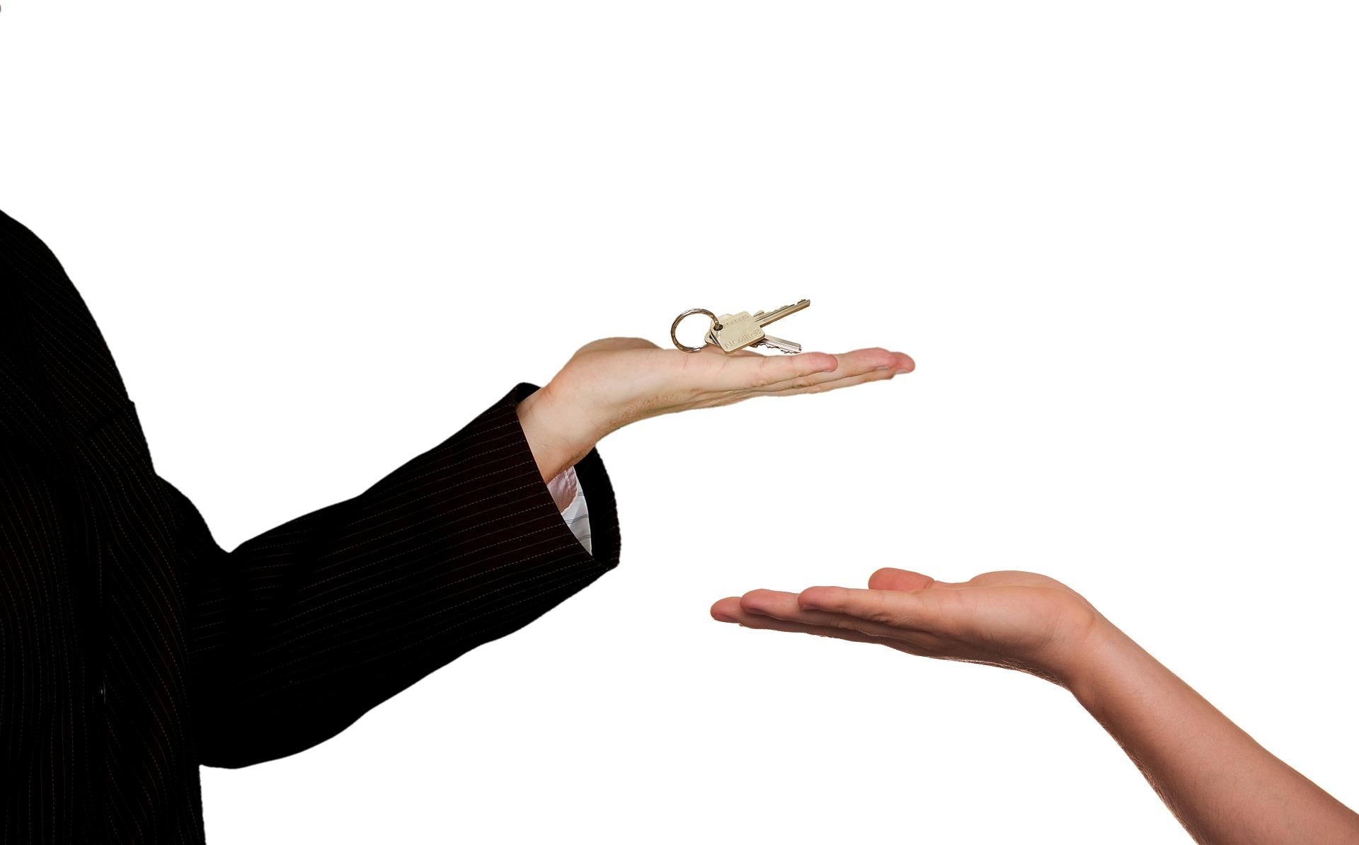 Eine Hand mit Schlüssel in der Hand und dadrunter eine weitere Hand die den Schlüssel entgegen nehmen will. Es geht um die Vermietung oder den Verkauf einer Immobilie.
