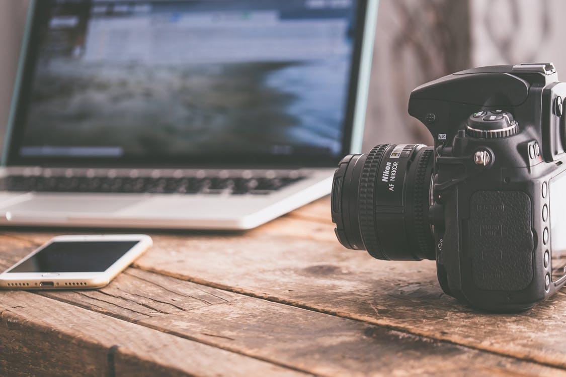 Holztisch mit Kamera, Smartphone und Notebook