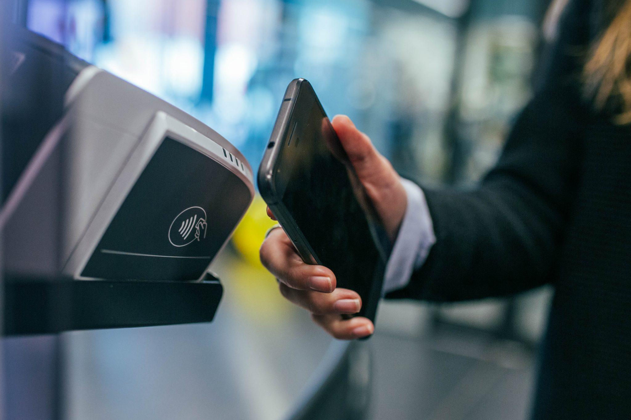 Eine Person hält sein Smartphone gegen ein Kassenterminal, um über Google Pay zu bezahlen