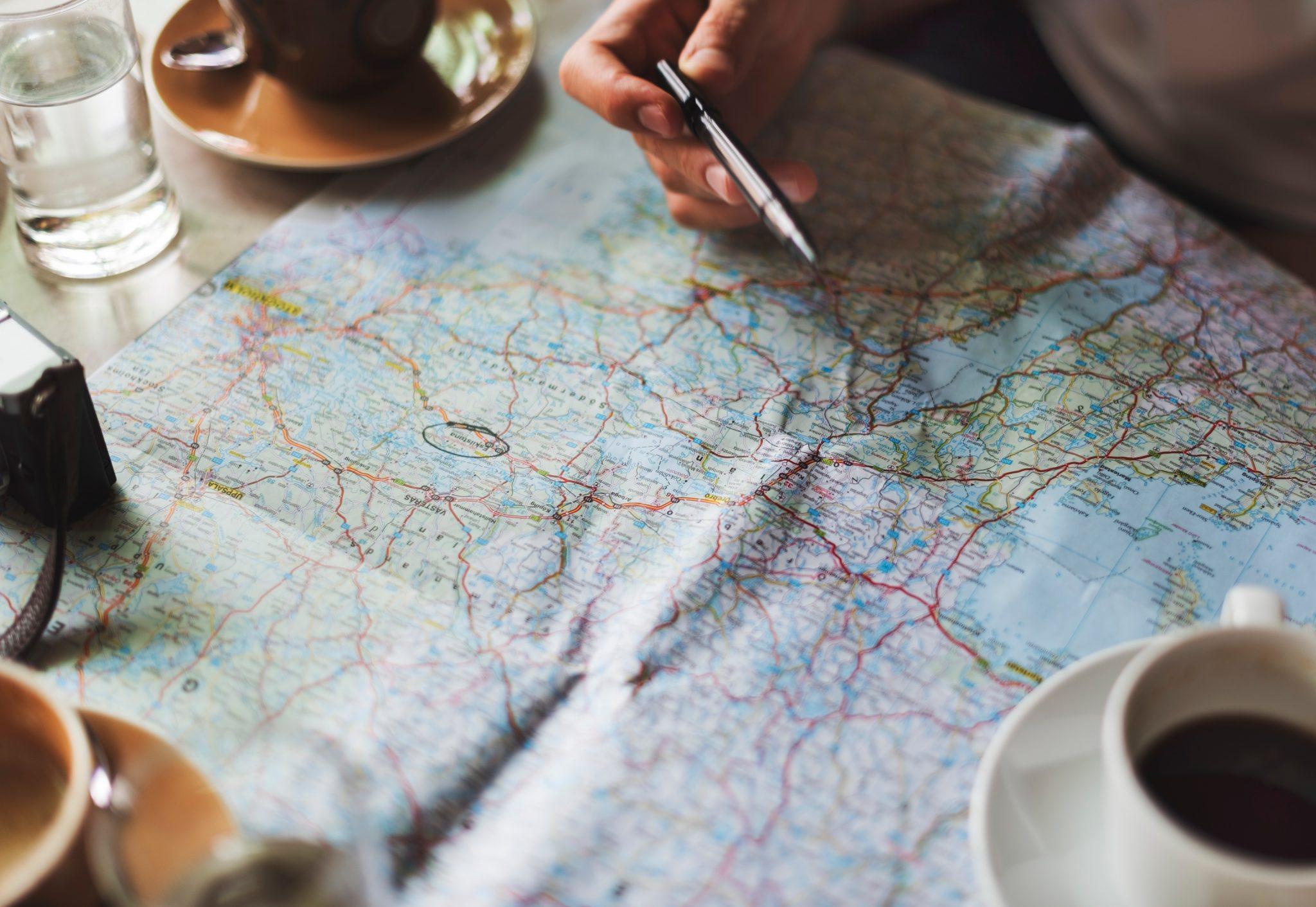 Bunte Landkarte mit Markierung auf der Kaffee steht und Hand liegt