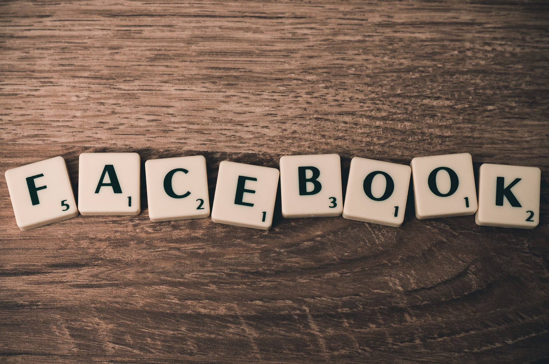 Holztisch mit Scrabble Steinen auf die denen Facebook steht