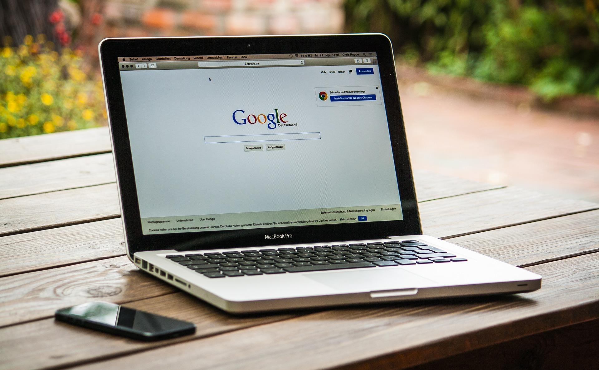 Macbook auf dem Google steht und Handy auf Holztisch