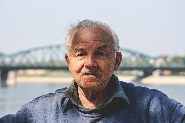 Älterer Mann vor Brücke und Fluss