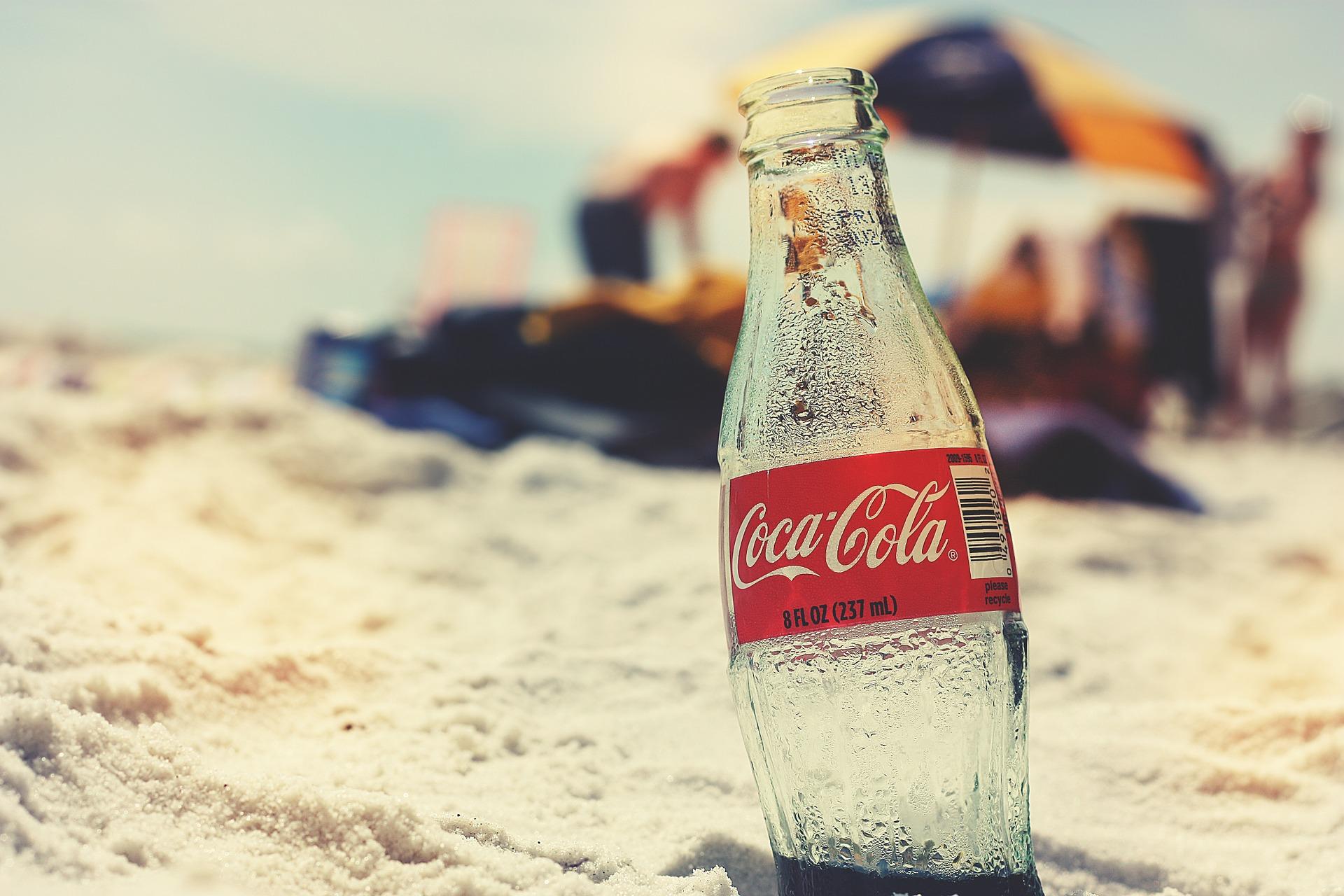 Cola Flasche im Vordergrund, im Hintergrund Strand