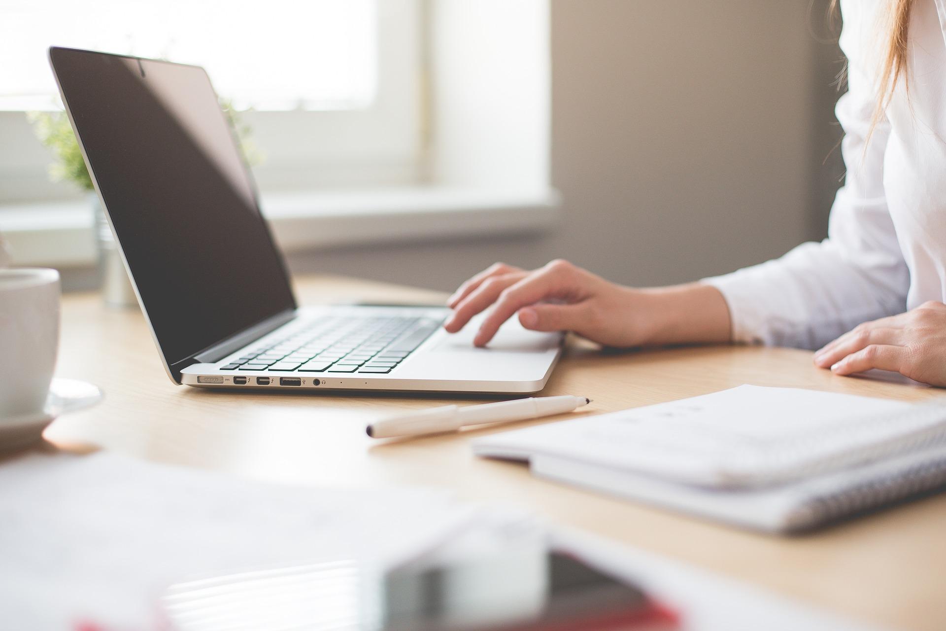 Frau sitzt mit Notizblock am Laptop
