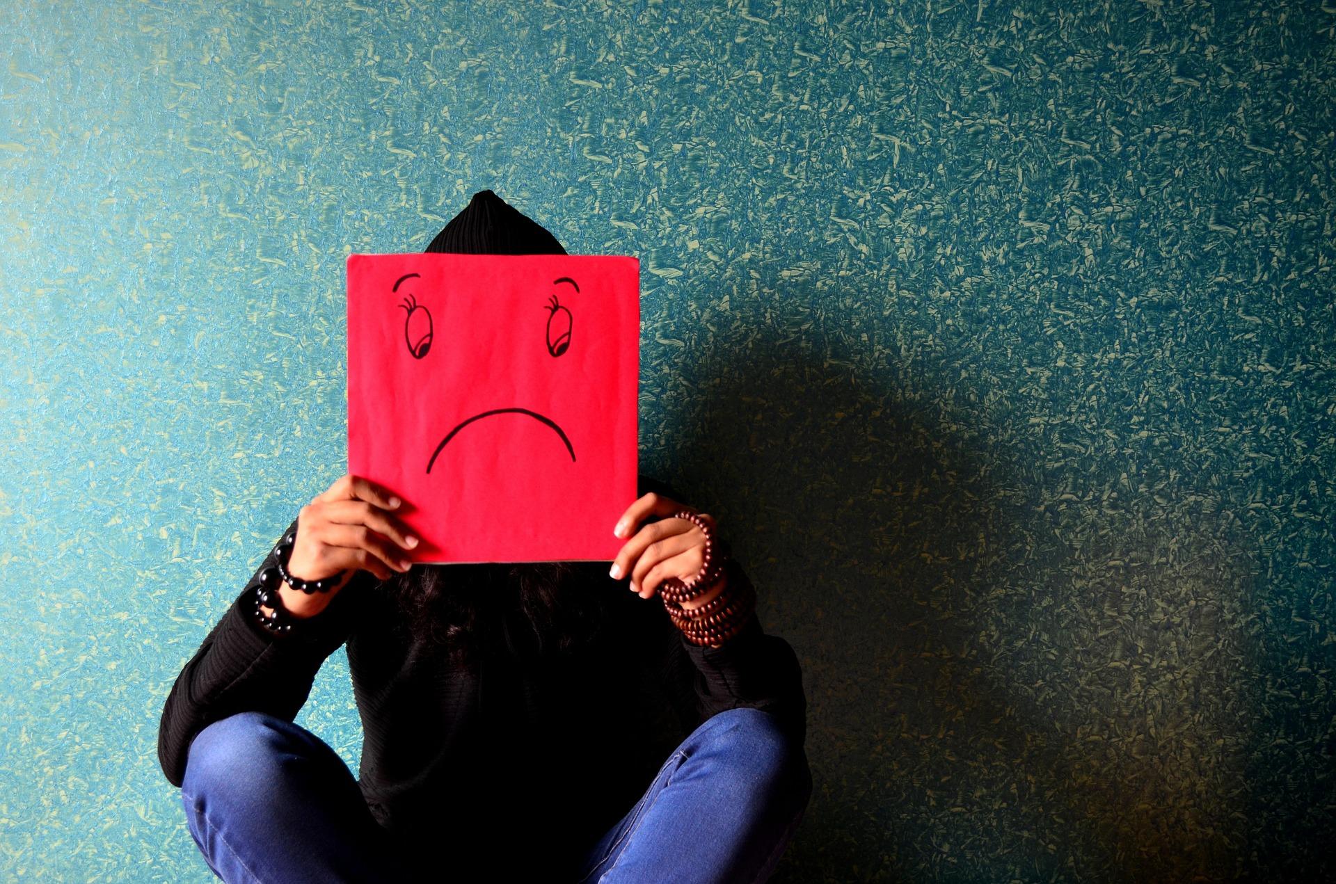 Frau sitzt auf dem Boden und hält sich eine rote Maske mit einem unzufriedenen Smiley vor das Gesicht
