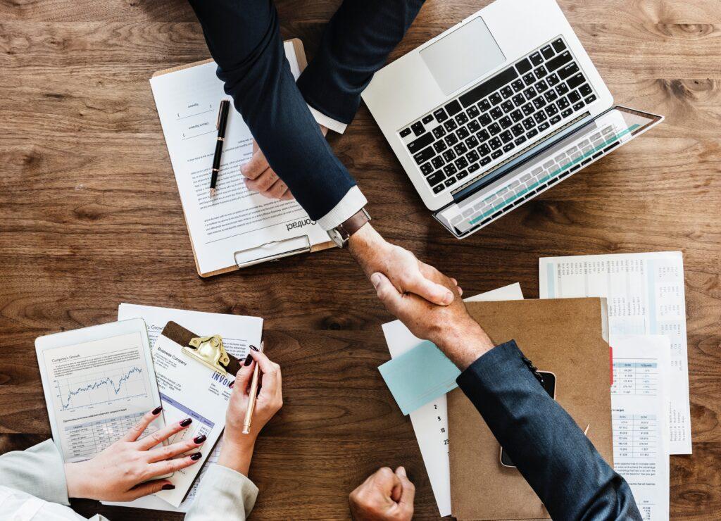 Händeschütteln über einem Schreibtisch - so gewinnst Du neue Kunden im Internet