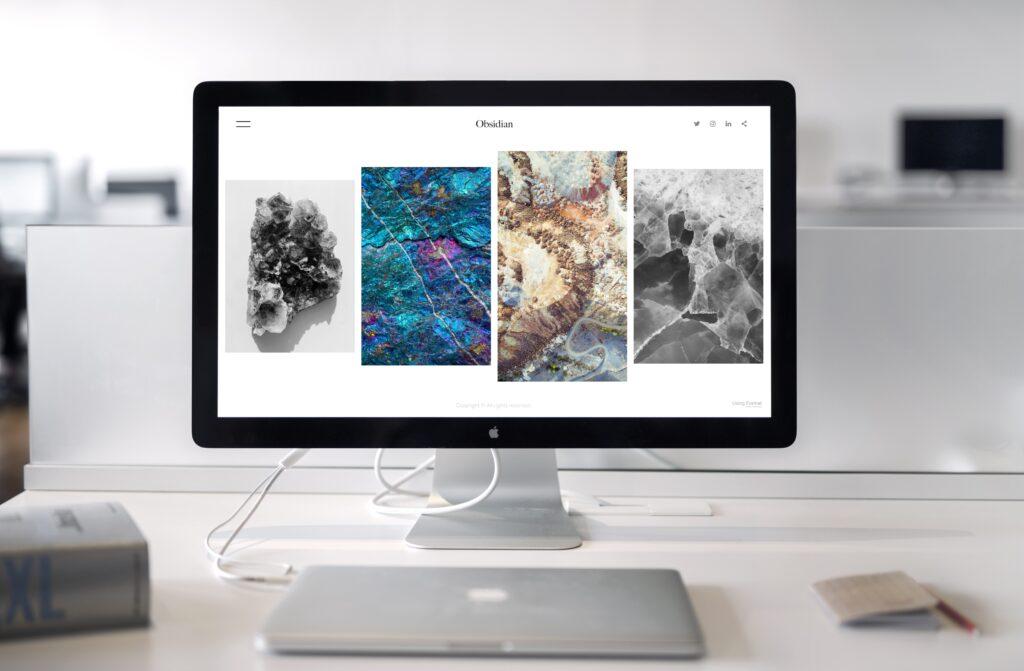 Großer Bildschirm auf weißem Tisch mit Macbook, Block und Buch davor