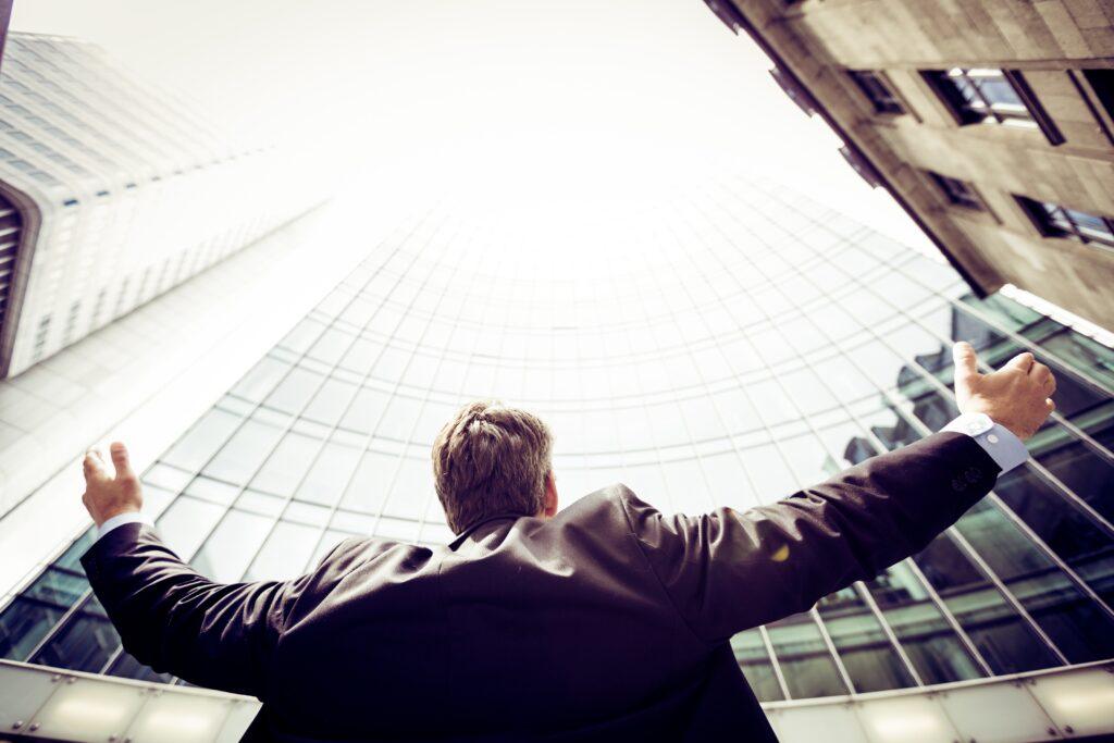 Mann im Anzug breitet seine Hände aus und schaut zu einem hohen Gebäude auf - Blogartikel zur Internetwerbung