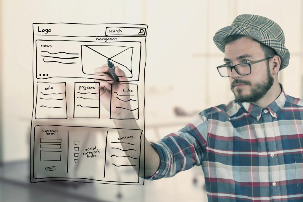Mann schreibt mit Edding auf Glas - Blog: Was braucht eine professionelle Webseite?