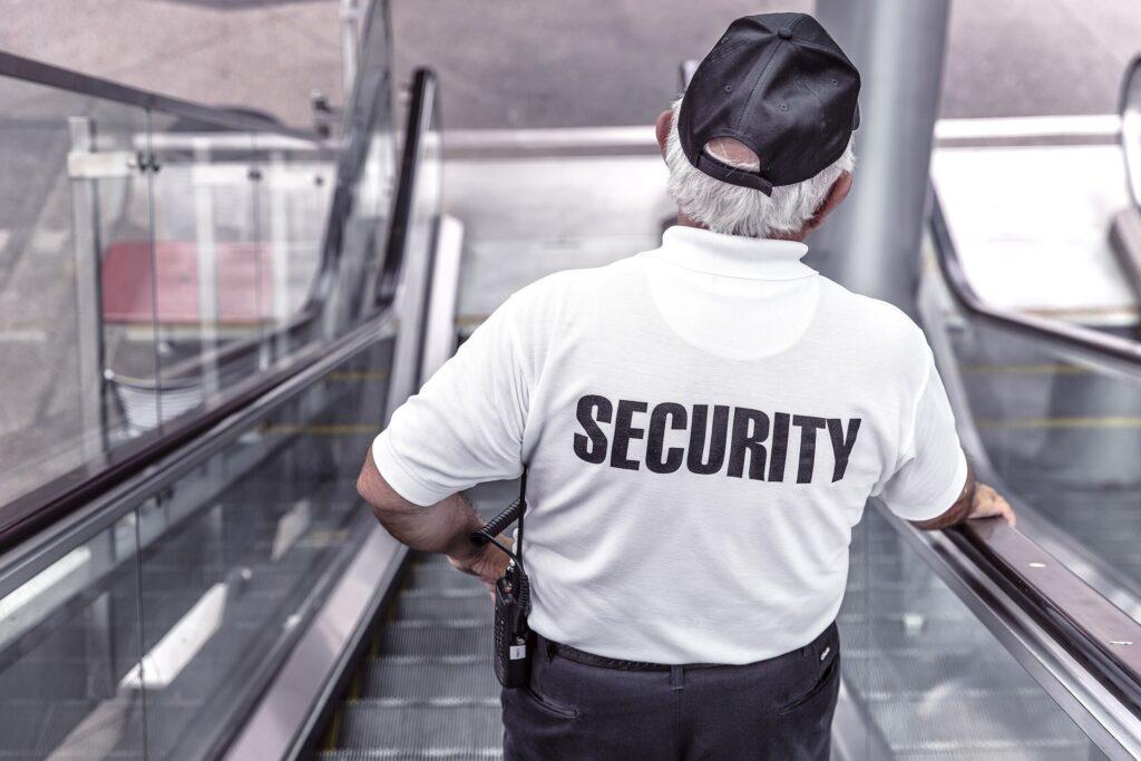 Mann auf Rolltreppe mit Rücken zur Kamera. Weißes Shirt auf dem Security steht. Blog Paragraph 13