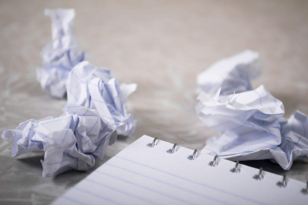 Schreibblock mit zerknüllten Blättern daneben. Zur Veranschaulichung des Blogbeitrags wie man einen guten Webtext schreibt.