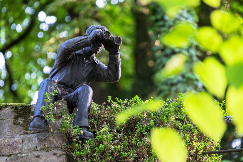Figur eines Mannes, der auf einer Mauer sitzt, sich herunter beugt und durch ein Fernglas schaut.