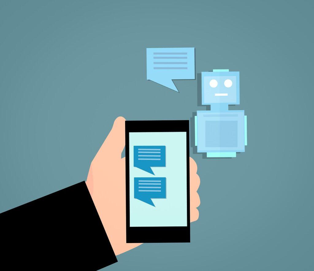 Grafik einer Hand, die ein Smartphone hält. Auf dem Display ein Chat. Im Hintergrund ein Roboter mit Sprechblase.