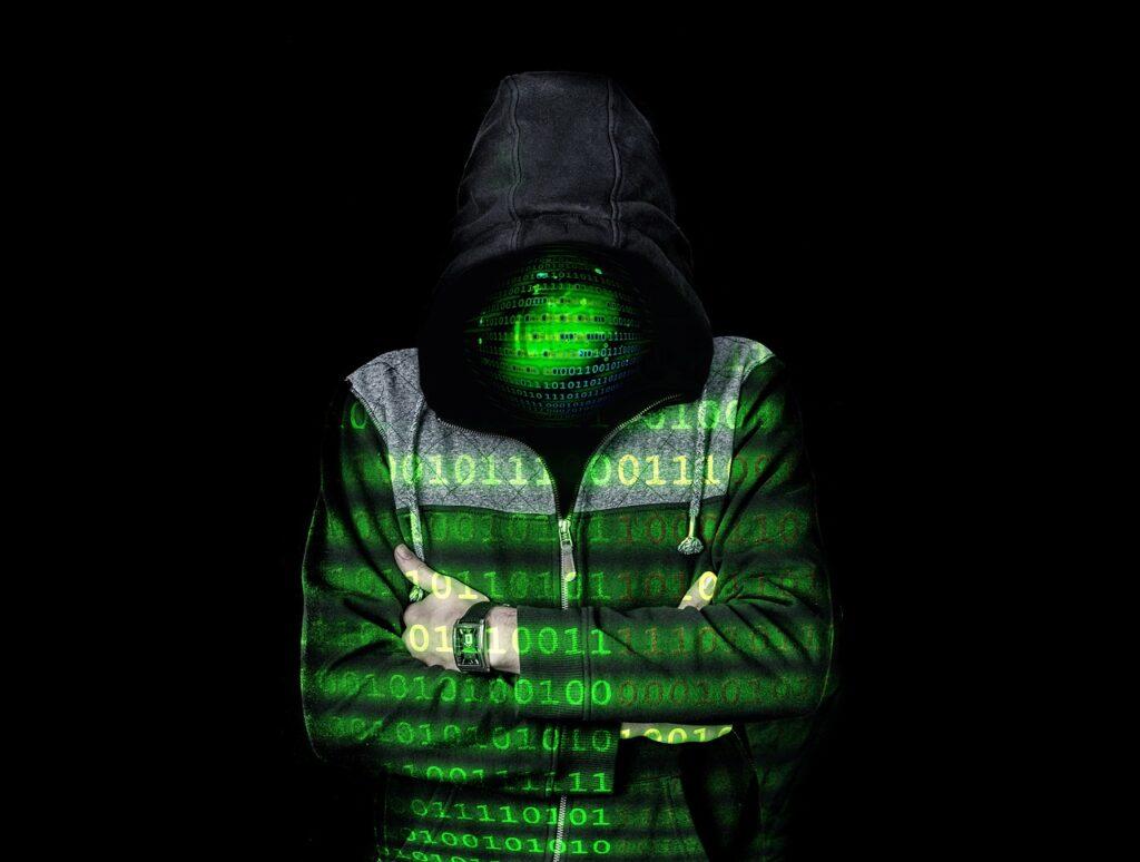 Ein Mann im Kapuzenpulli vor schwarzem Hintergrund, auf ihm in grün Nullen und Einsen projiziert. Sein Gesicht nicht zu erkennen, ersetzt durch grüne Nullen und Einsen.