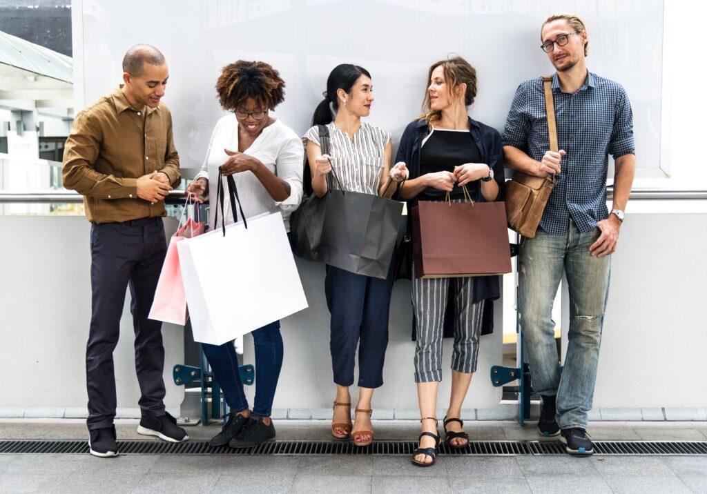 Mit glückliche Leute mit Shoppingtüten vor weißer Wand