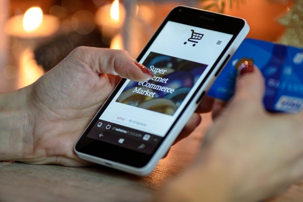 Frau mit Smartphone und Kreditkarte in der Hand