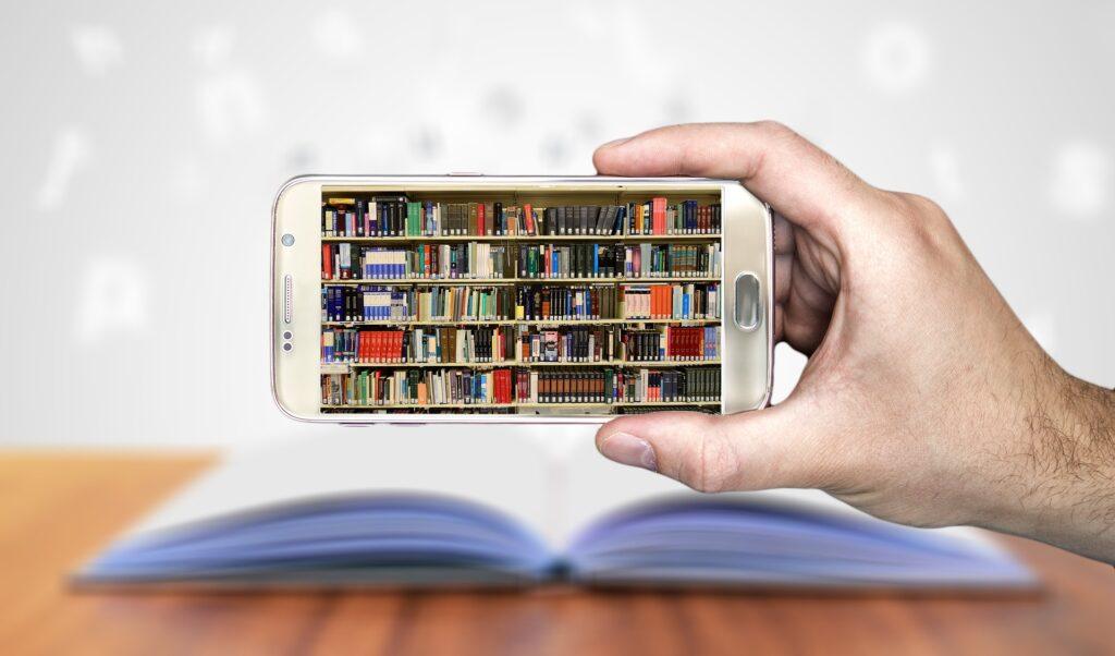 Eine Hand hält ein Smartphone, im Display ist ein volles Bücherregal zu sehen. Im Hintergrund liegt ein aufgeschlagenes Buch auf einem Tisch, aus dem Buchstaben herausfliegen.