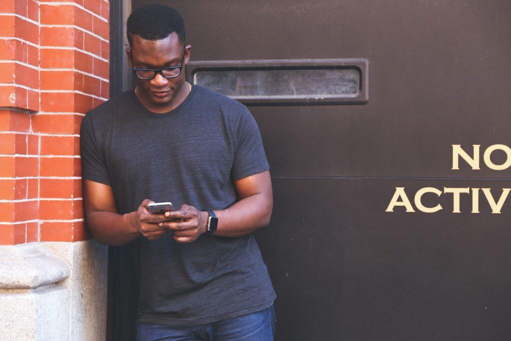 Ein Mann lehnt mit der rechten Schiulter an einer Hauswand und schaut auf sein Smartphone, das er in beiden Händen hält.