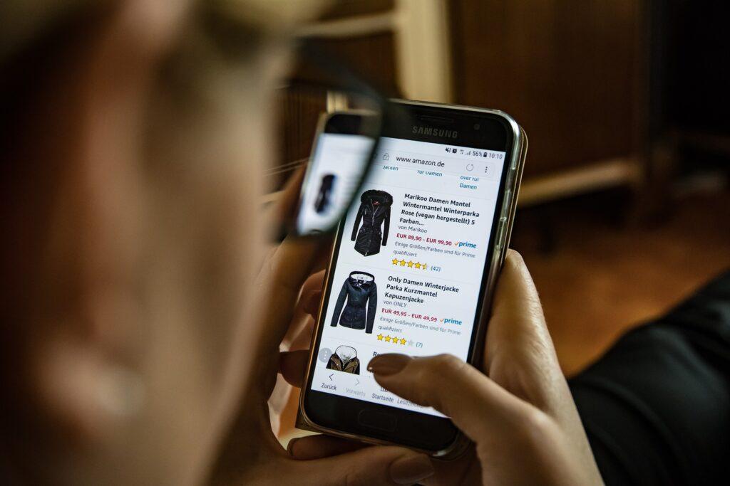 Frau mit Smartphone sucht auf Amazon