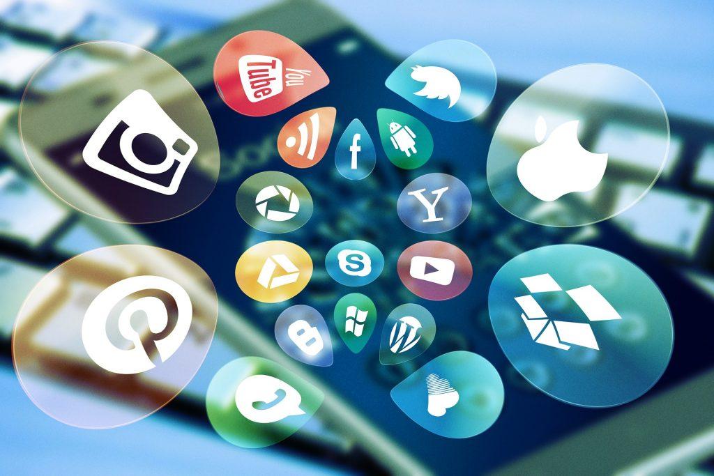 Viele Blasen mit Icons von Social Media und Programmen fliegen aus einem Smartphone Bildschirm.