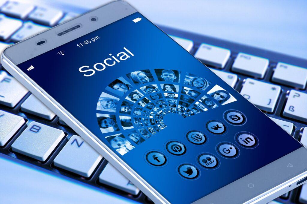 Ein Smartphone liegt auf einer Tastatur. Auf dem Bildschirm sind verschiedene Icons von sozialen Medien zu sehen.