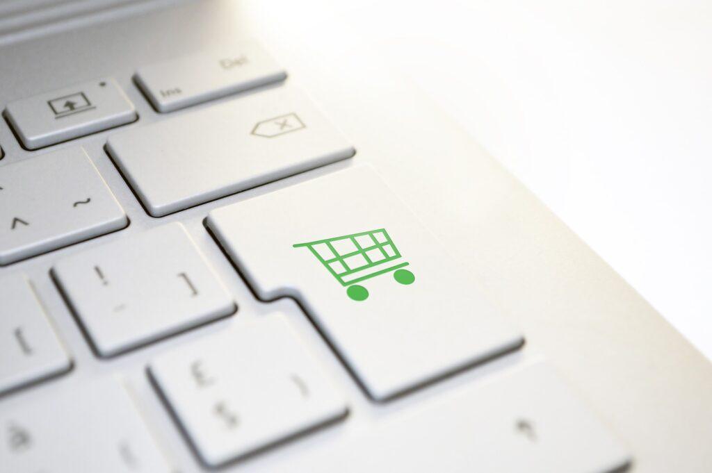 Ausschnitt einer weißen Tastatur, auf deren Enter-Taste sich ein grüner Einkaufswagen befindet.