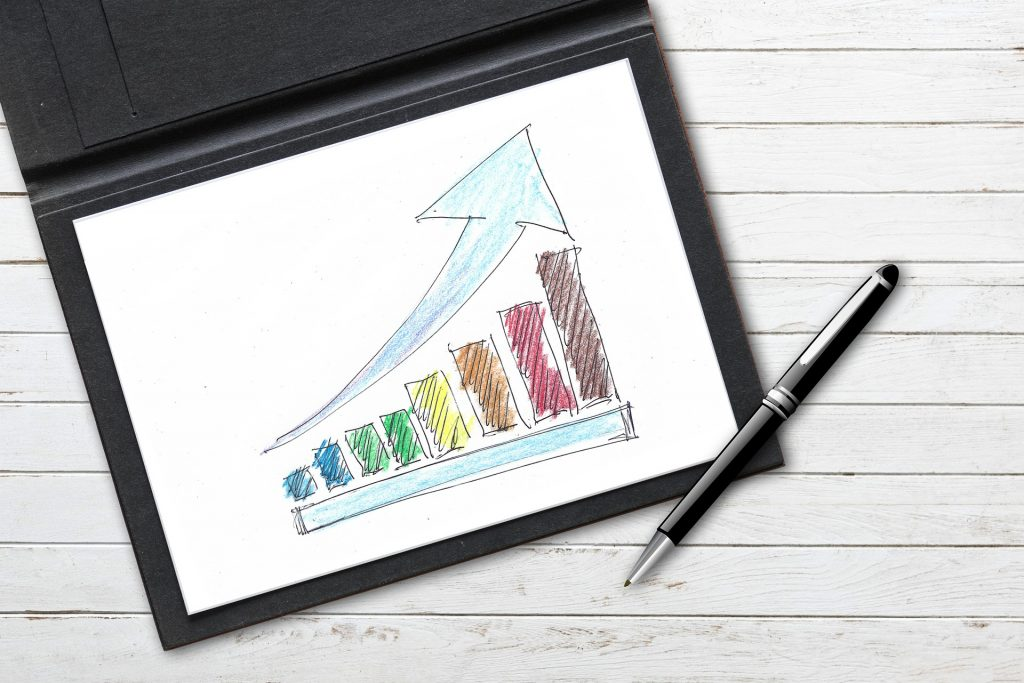 Eine Zeichnung eines Diagramms, das nach rechts hin ansteigt mit einem Pfeil, der die Steigung anzeigt. Die Zeichnung liegt in einer Mappe auf einem Tisch. Ein Kugelschreiber liegt auf der Kante der Mappe.